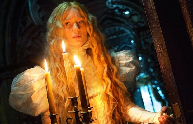 a blonde girl holds a candelabra and looks frightened in crimson peak