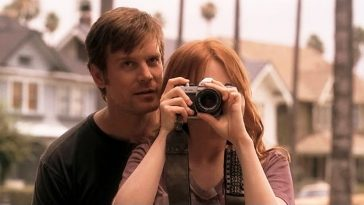 nate whispers in claire's ear as she takes a photo