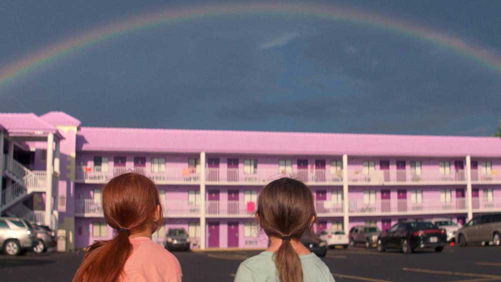 2 young girls look at a rainbow above a pink motel