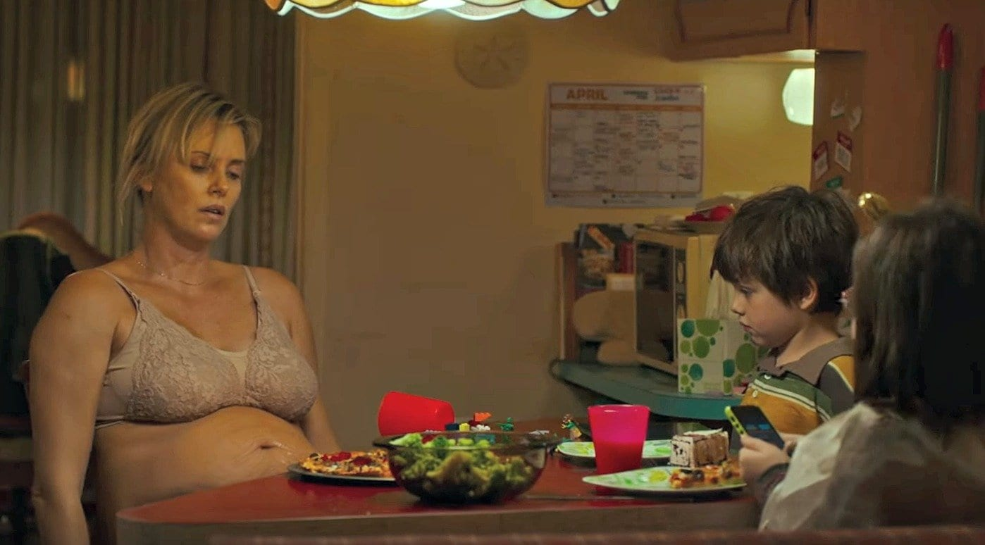 Heavily pregnant Charlize Theron sits a the dinner table with her two children in Tully