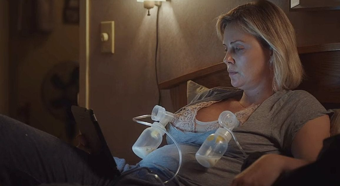 Charlize Theron as Marlo Moreau, sitting with two breast pumps attached in Tully