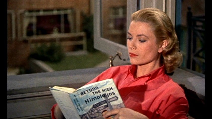 Kelly pretends to read Beyond the Himalayas to impress her man, in Rear Window
