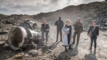 The Thirteenth Doctor and her companions look off into the distance.