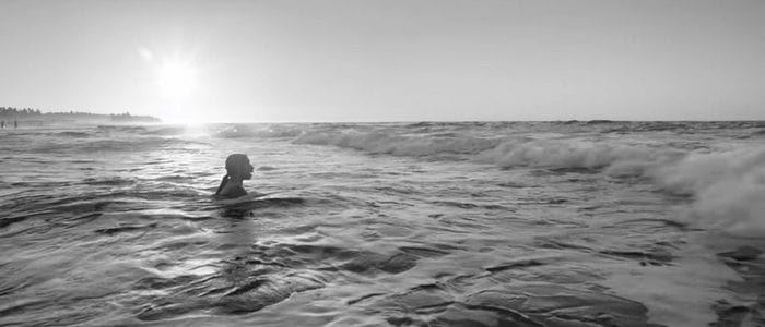 Cleo wades into the ocean in this still from Roma.