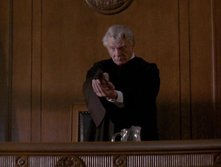 Steve Forrest as Judge Murdoch holding a gun in his bench