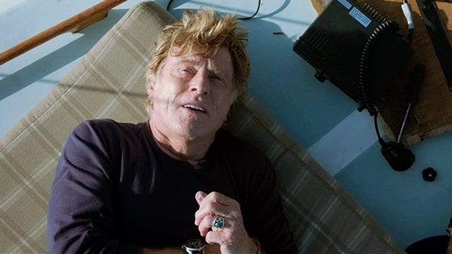 Robert Redford lies on the boat deck looking up at the sky in All is Lost