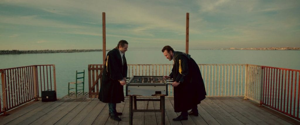 Marco Giallini and Jerzy Stuhr play table football on a deck overlooking the sea