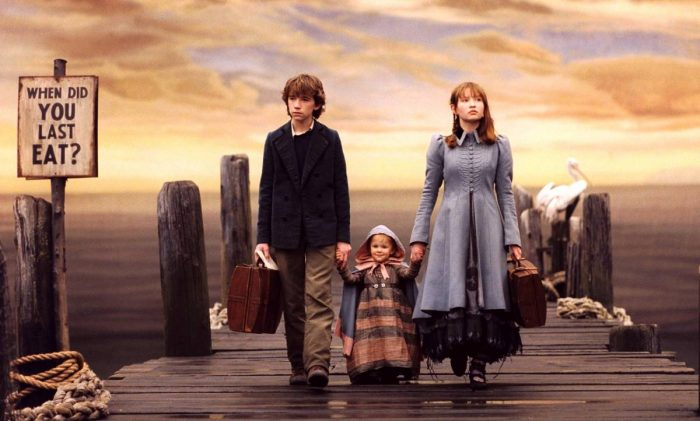 Violet Baudelaire and her brother Kraus stand on a deck with their baby sister Sunny where they wait for Lemony Snicket