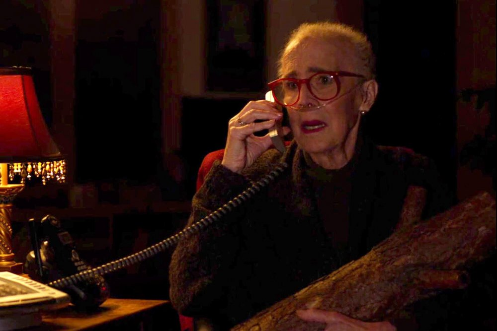 Margaret Lanterman, in dwindling health, speaks on a land line phone in her mostly dark room.  There is a lamp with a red lampshade to the left. She is seated in a chair.