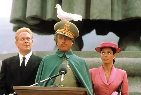 Roberto Strausmann and Madonna stare at a bird on Jack Noah's head while pretending to be President Alfonse Simms