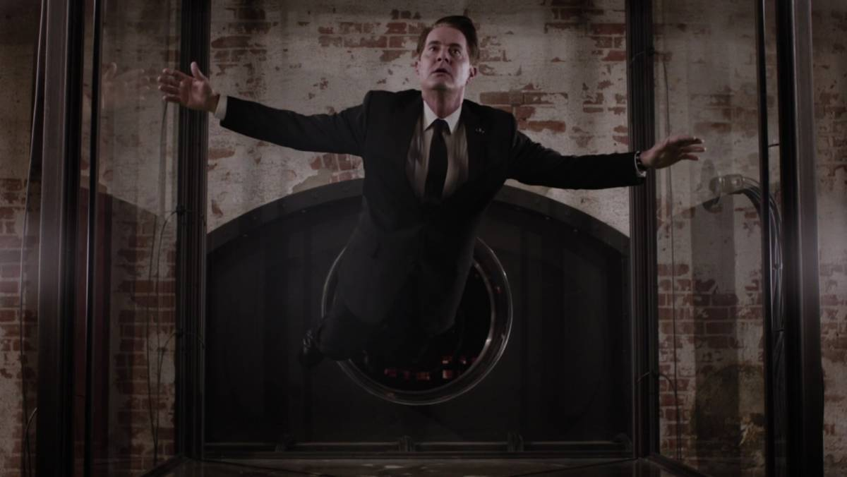 Dale Cooper floats inside a glass box in a sparse room with brick walls in New York.
