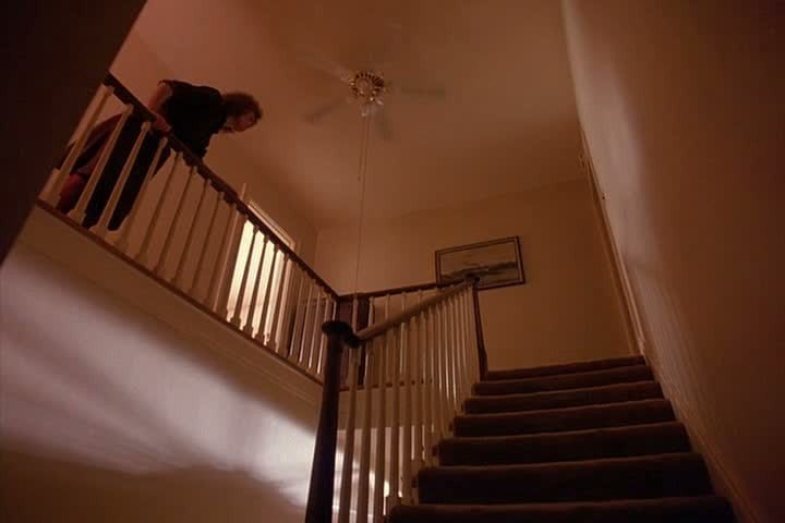 Sarah Palmer stands at the top of her stairs under the ceiling fan