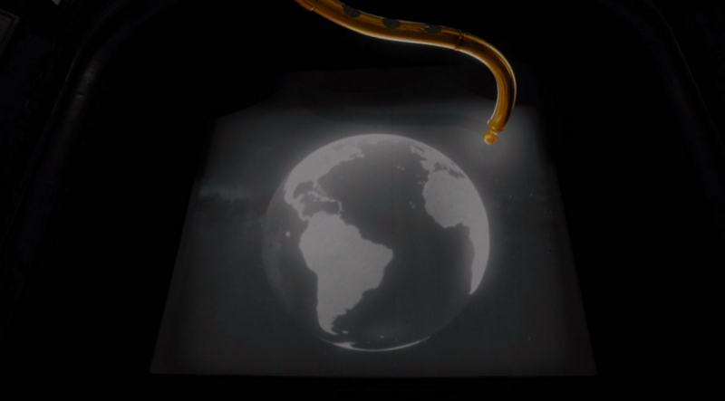 The earth in black and white with a golden tube reaching into it on a screen