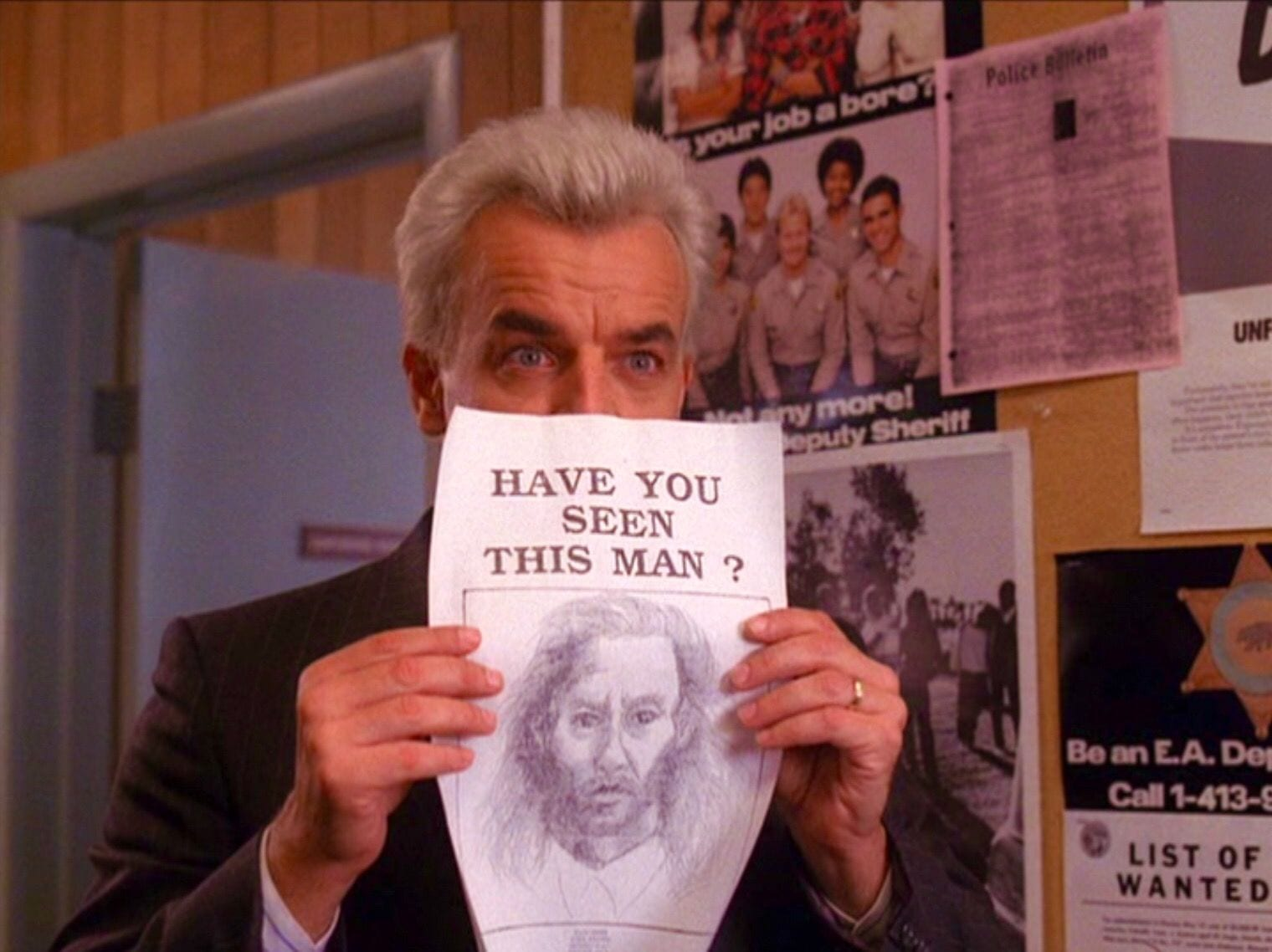 Leland Palmer holds up the artist impression picture of Bob