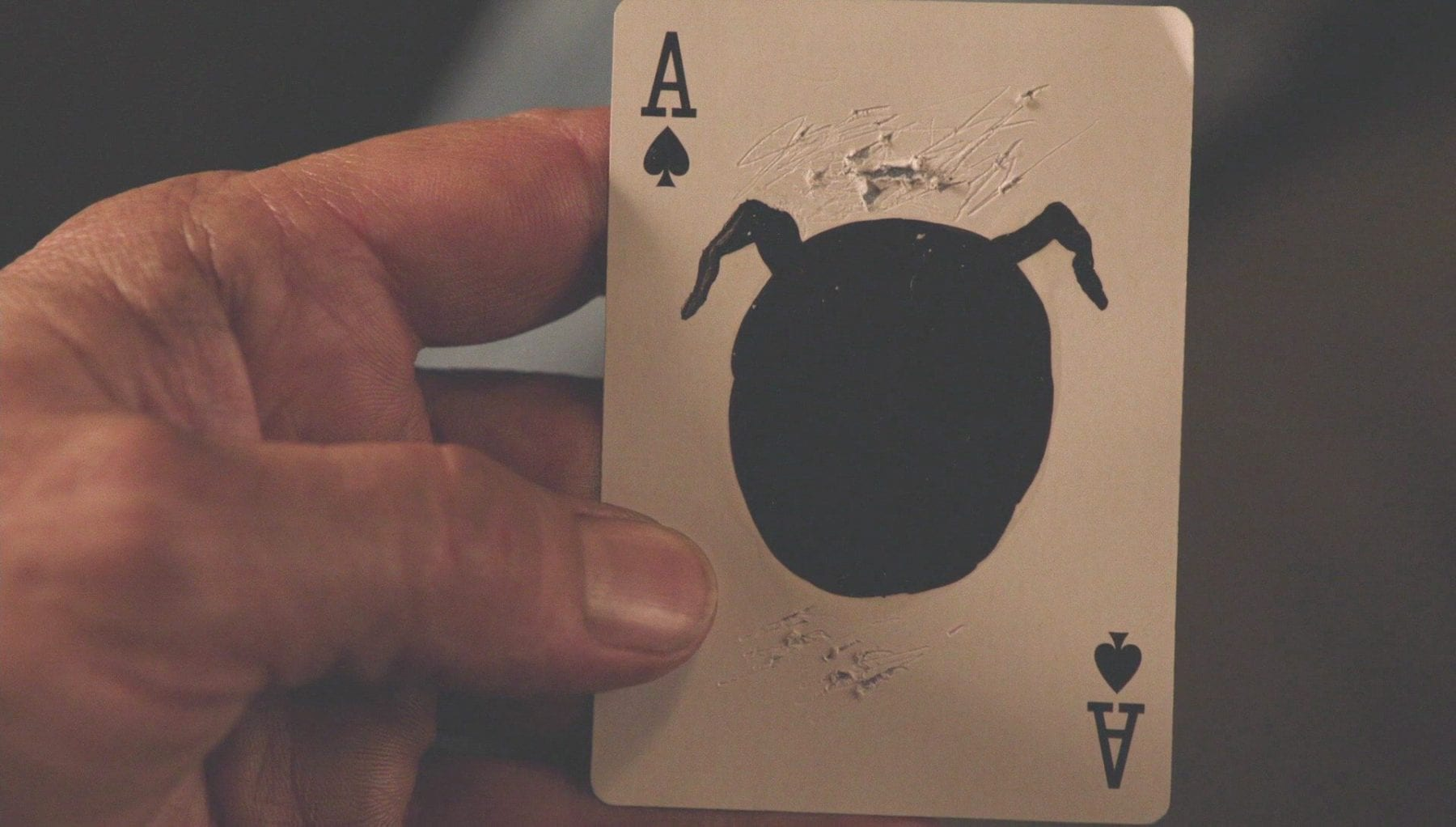 Ace of spades card with black circle with horns painted over the spade