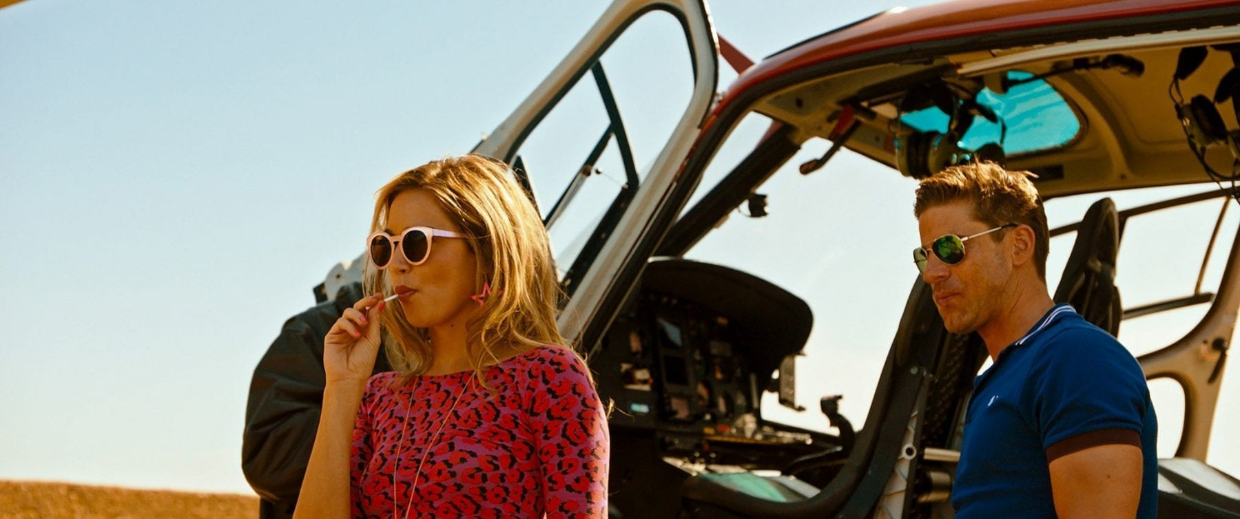 Our female lead steps out of a helicopter wearing shades and sucking a lollipop