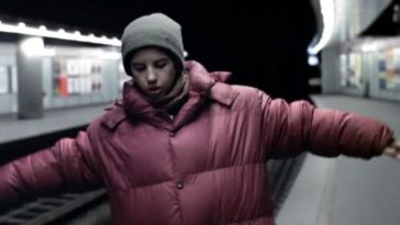 a boy in a red coat walks along an underground train track cautiously