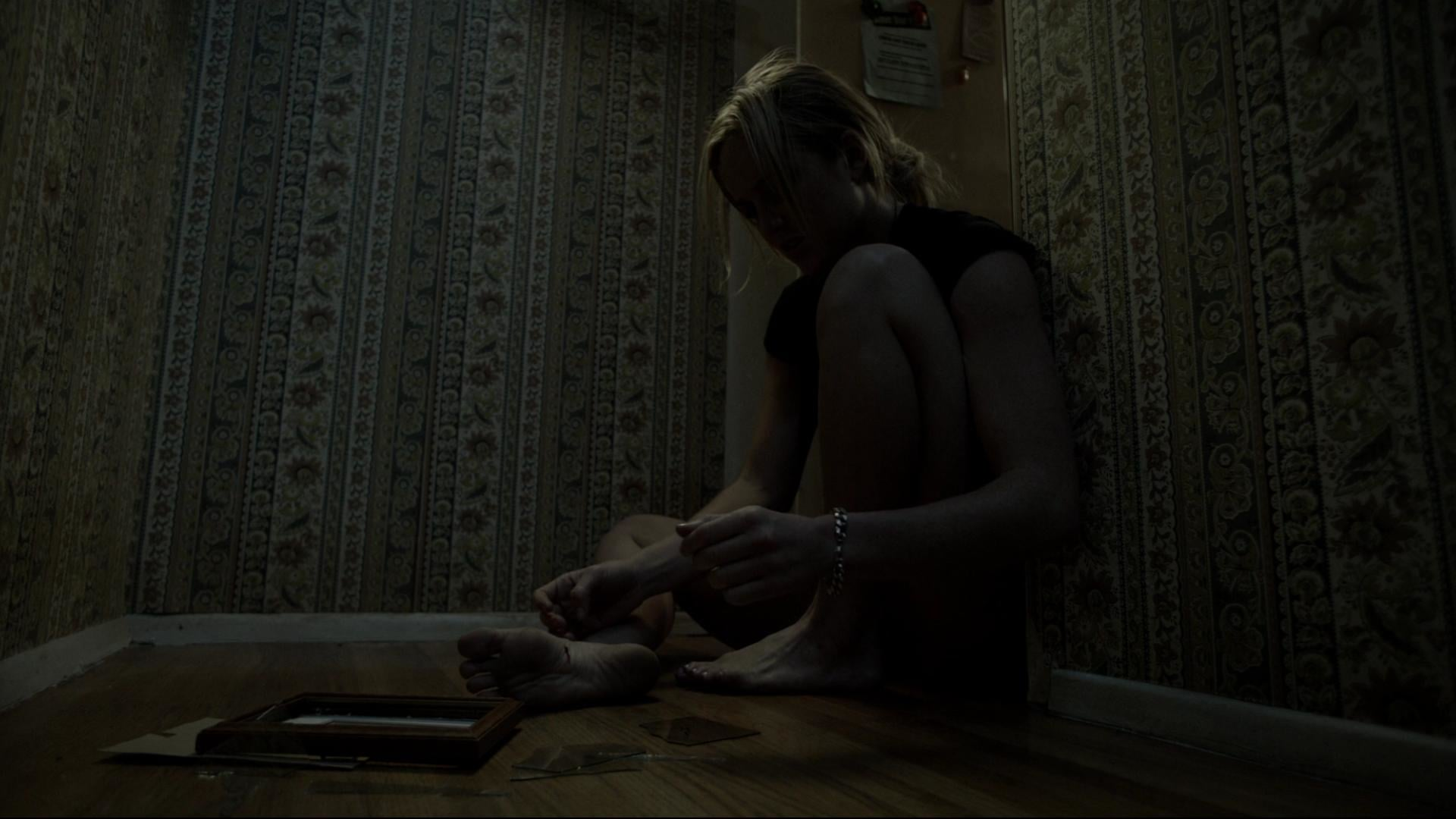 Annie (Caity Lotz) picks up the pieces of a broken picture in The Pact