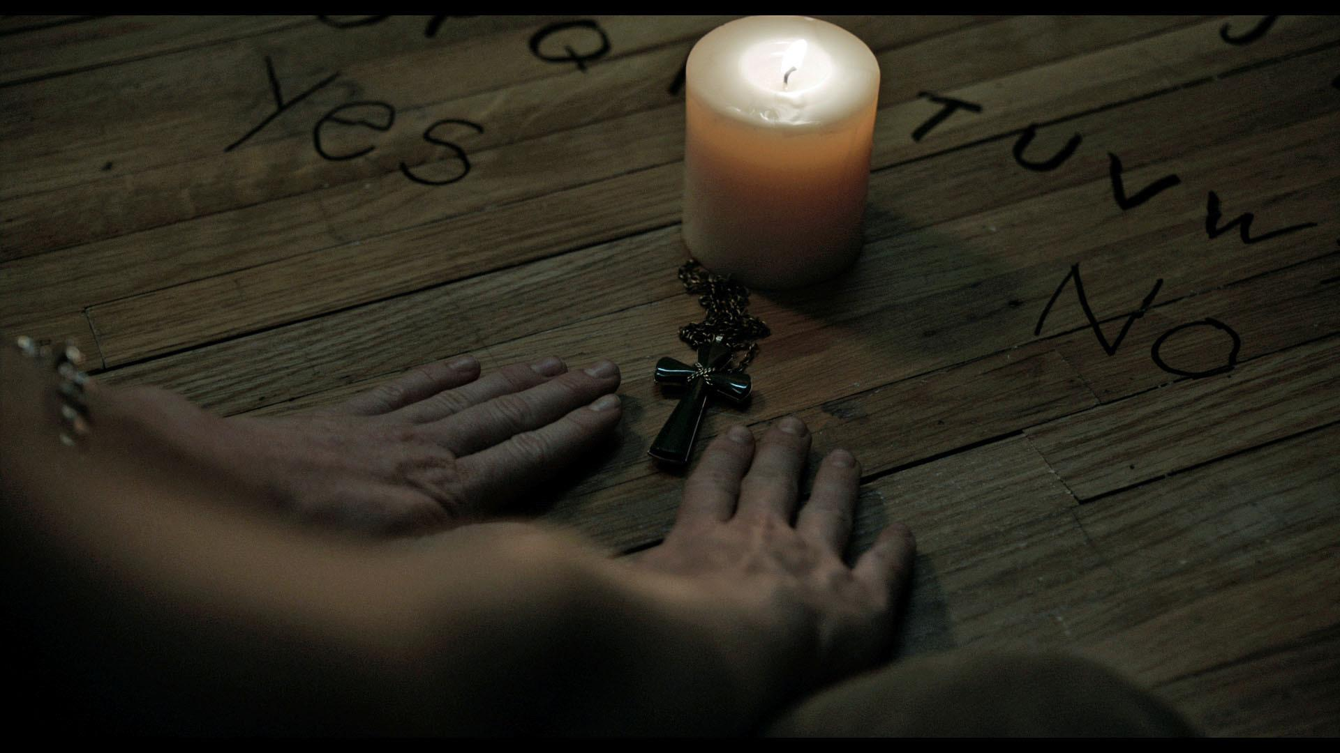 Annie uses a cross and a candle to contact the dead through a ouija board