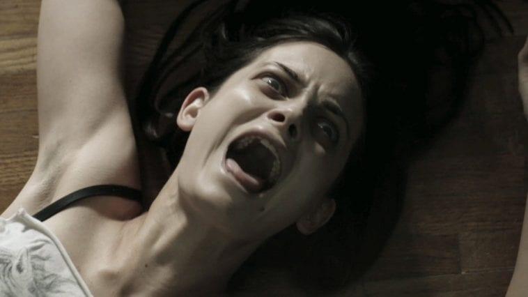 a woman screams as she's dragged across the floor