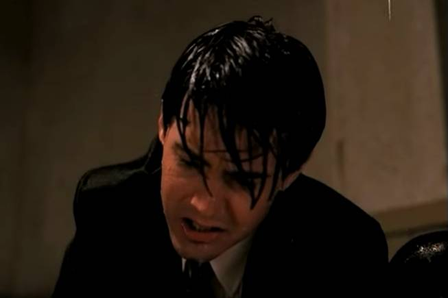 A wet Agent Cooper kneels over Leland Palmer