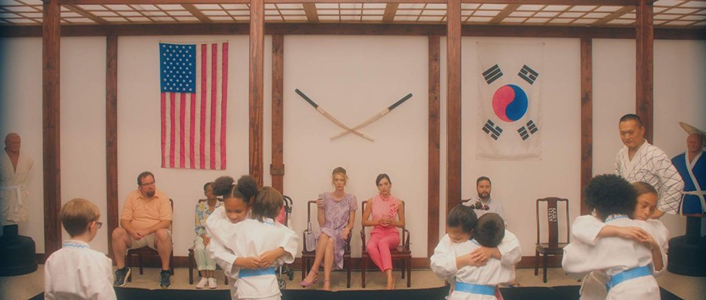 Lisa (left) and Jill (right) sit next to each other while their are in a karate class. There are children hugging in the foreground.