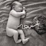 a newborn baby lying next to its placenta, the word love spelled out with the umbilical chord