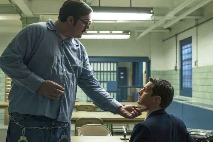 Ed Kemper (Cameron Britton) towers over agent Holden Ford (Jonathan Groff) during an interview in Mindhunter Season 1