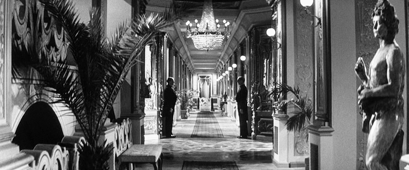 An opulent corridor with chandeliers and waiters