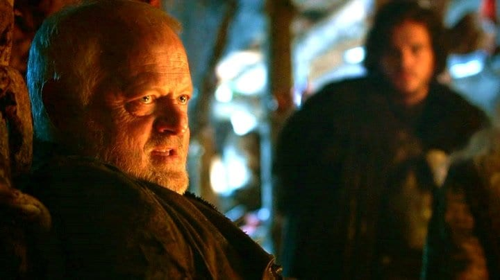 Craster hosts the Night's Watch in his keep, with Jon Snow in the background