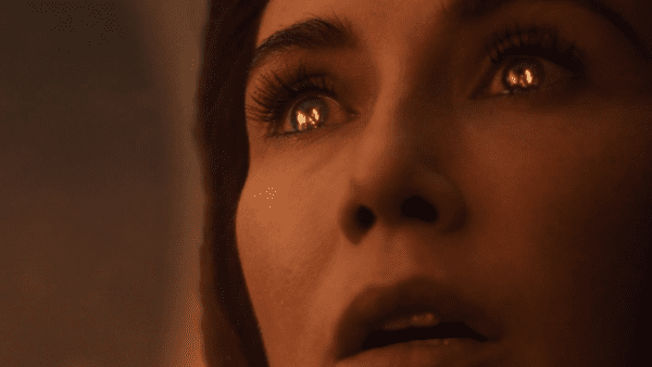 Melisandre's eyes reflect the fire as she lights up the swords in Game of Thrones The Long Night