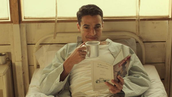 Yossarian holds a book and cup while lying in a medical bed in Catch-22