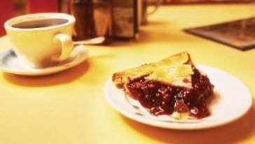 a cup of coffee and a slice of cherry pie on a counter