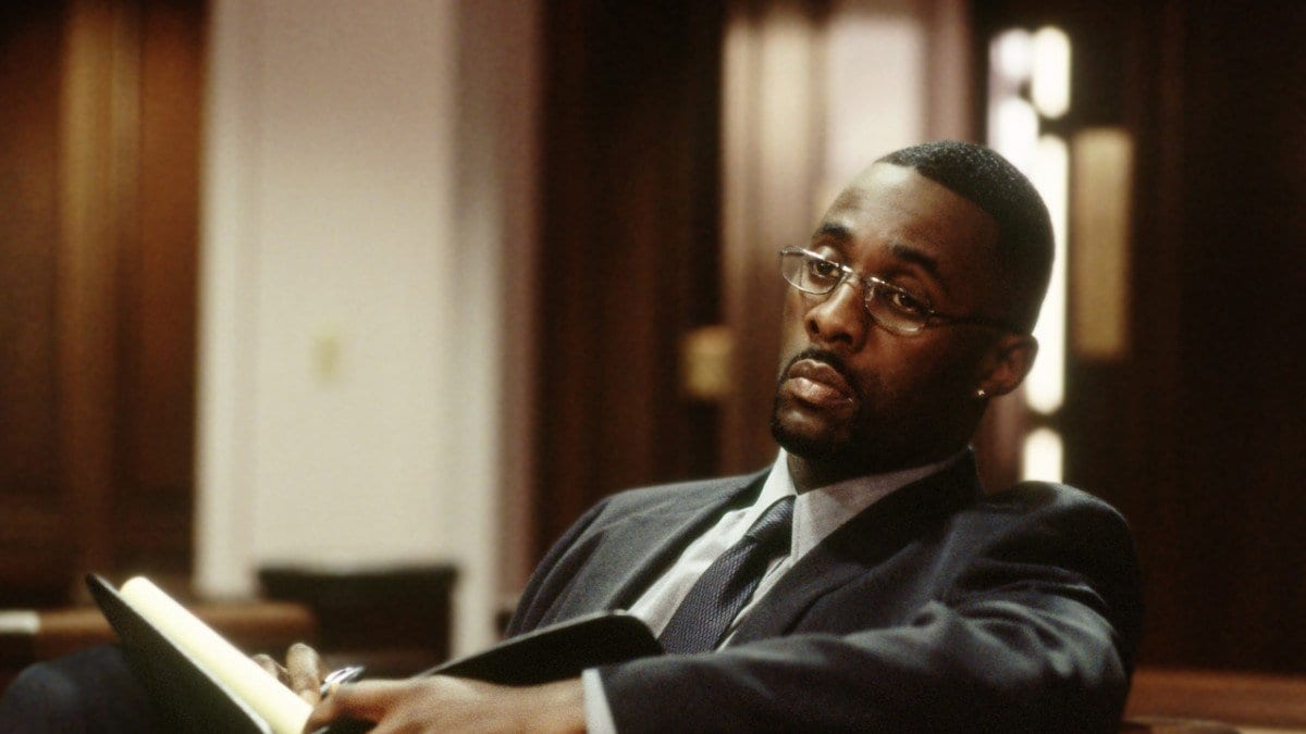 Stringer Bell (Idris Elba) sits in a courtroom wearing glasses and holding a book in The Wire's pilot episode