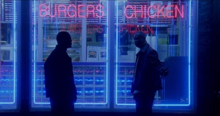 D'Angelo and Wee-Bey stand in front of the neon signs of a restauant in The Wire's pilot episode