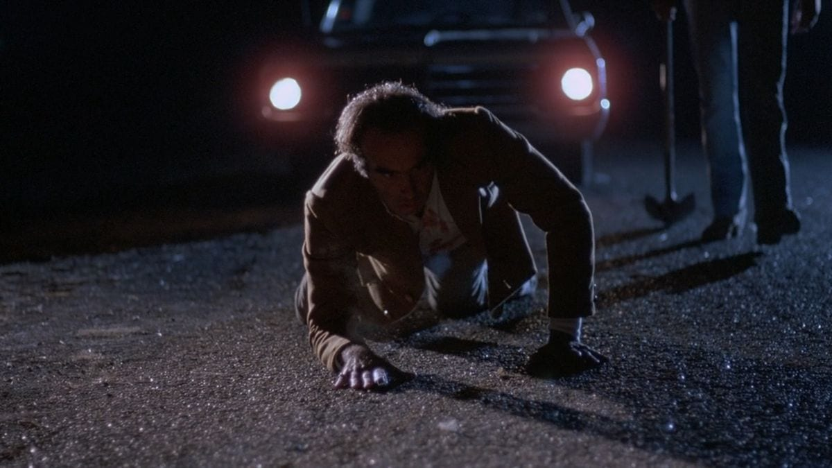 Marty (Dan Hedaya) crawls away from Ray (John Getz) and his shovel.