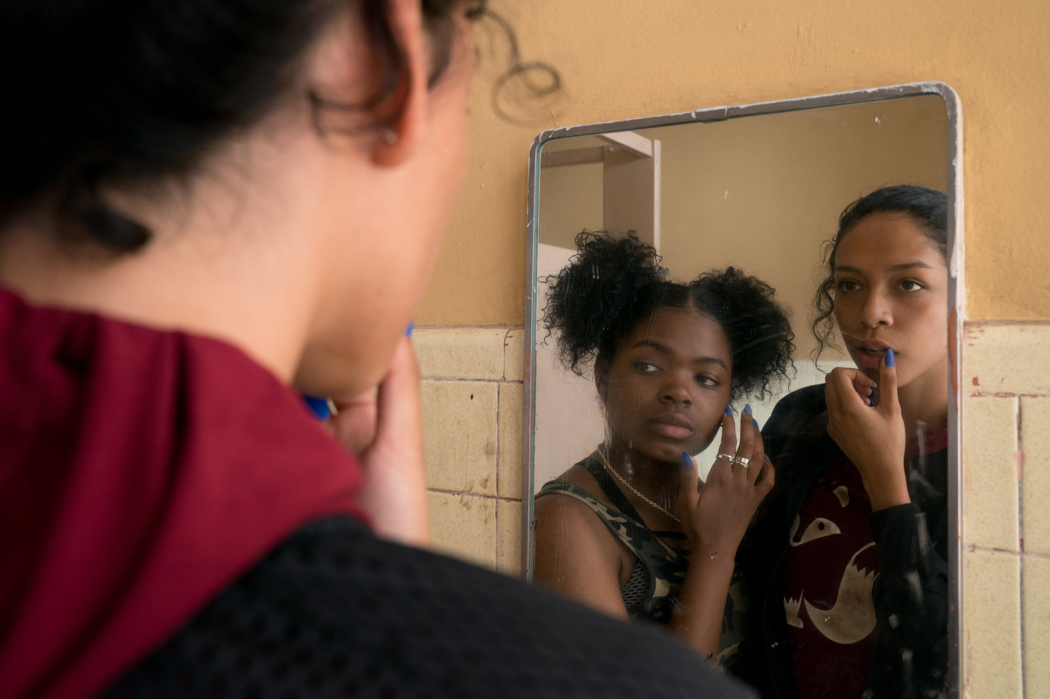Sasha and Yvonne looking at themselves in a mirror at school in Chambers