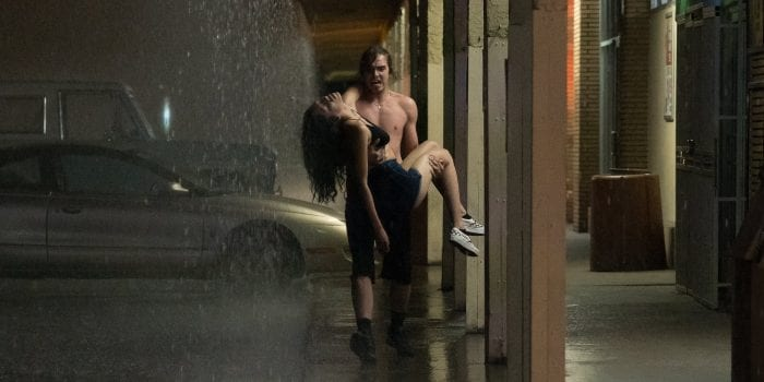 TJ (Griffin Powell-Arcand) carries Sasha (Sivan Alyra Rose) in the rain after her heart attack