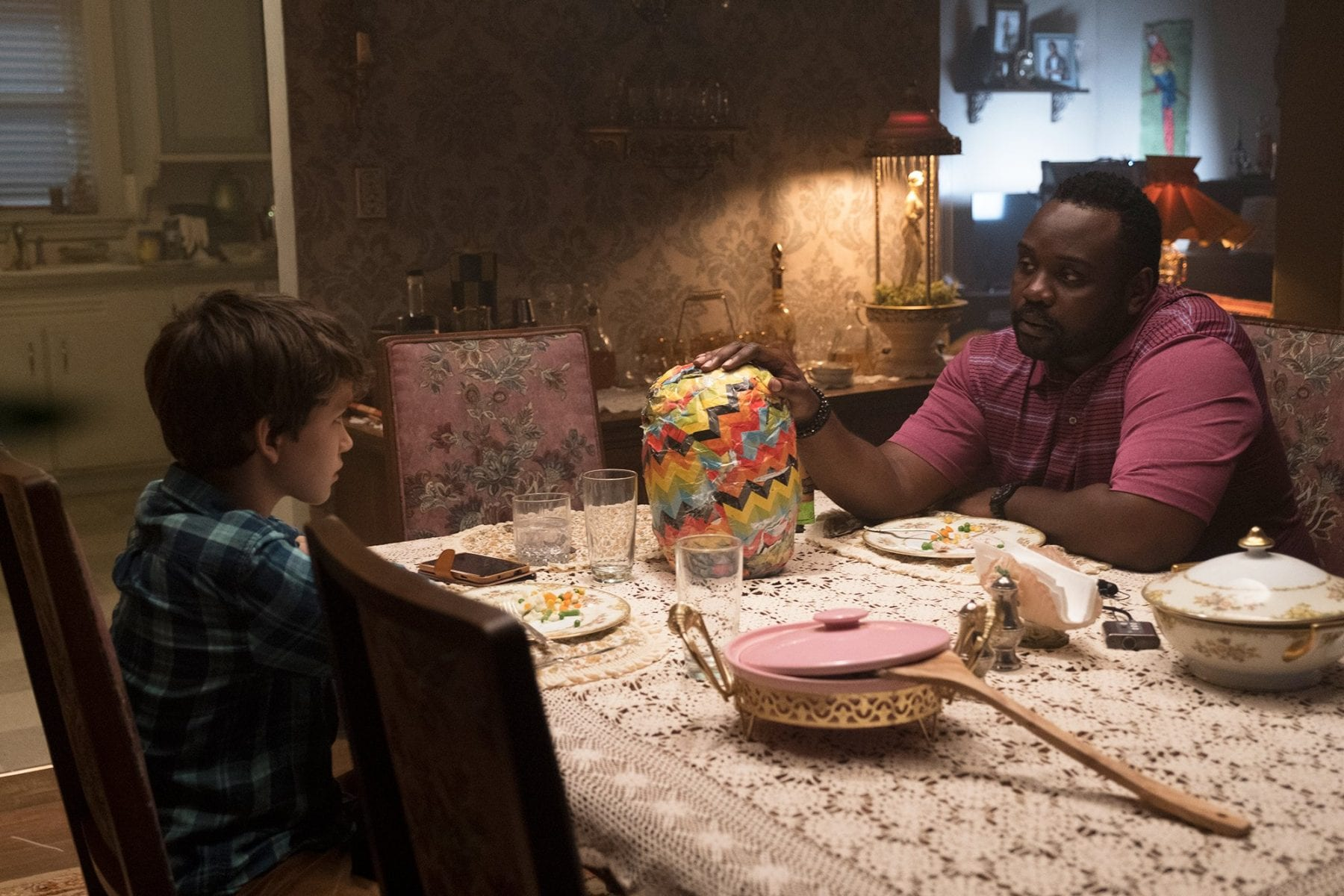 "Detective Mke Norris (Brian Tyree-Henry) and Andy (Gabriel Bateman) talk over dinner, a strange ""gift"" in between them."