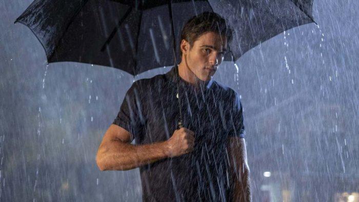 Nate (Jacob Elordi) holds an umbrella in the rain in Euphoria