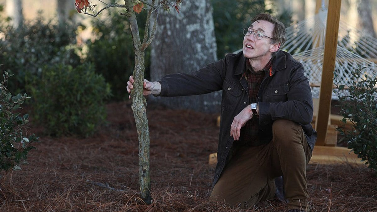 Dr. Jason Woodure (Kevin Durand) kneels holding a branch in Swamp Thing.