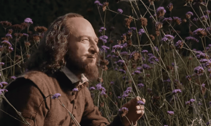 kenneth branagh as william shakespeare in tudor costume smelling flowers in a field