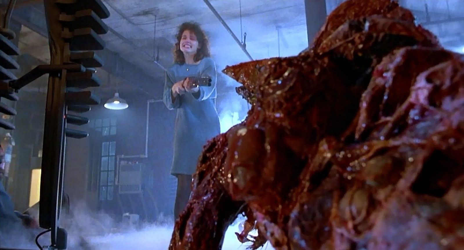 Geena Davis as Veronica holding a gun towards The Fly
