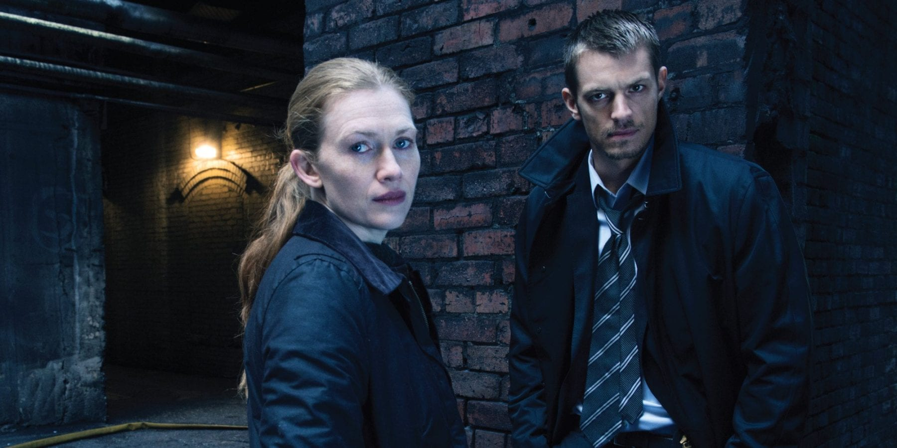 Sarah Linden (Mireille Enos) and Stephen Holder (Joel Kinnaman) look on in AMC's The Killing