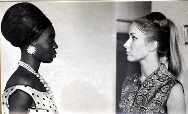 A Black Senegalese woman and her white French employer look squarely at one another in a tense scene.