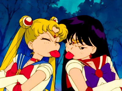 usagi (sailor moon) and rei (salior mars) sticking out their tongues at one another