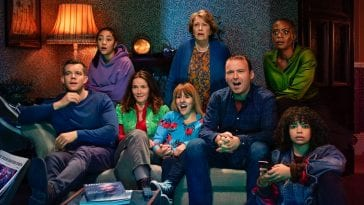 The cast of Years and Years sit and stand in a living room