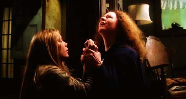 Carrie White (Sissy Spacek) and Margaret White (Piper Laurie) pray in Brian DePalma's Carrie (1976).