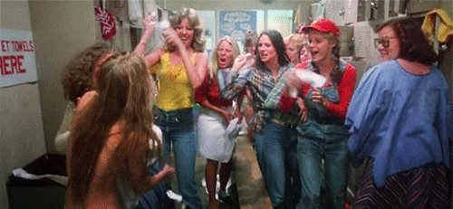 A group of girls in a locker room laugh and throw tampons at nude Carrie White (Sissy Spacek).