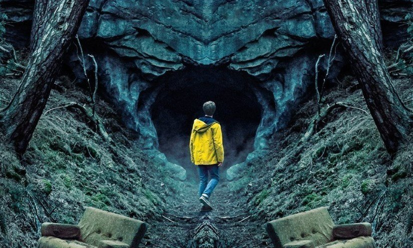 Jonas Kahnwald in a yellow coat standing next to chairs and looking into the Winden cave in Netflix's Dark